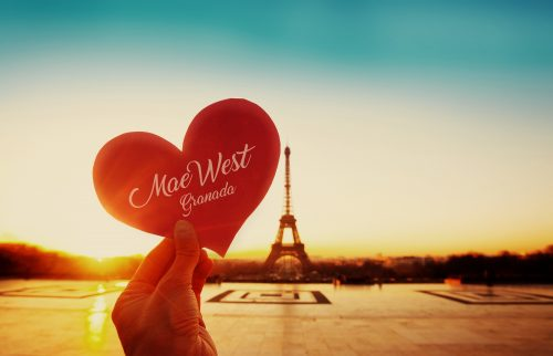 beautiful vintage card from Paris, Eiffel tower and hand with paper heart at sunrise